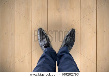 Businessman standing isolated on white background against wooden planks