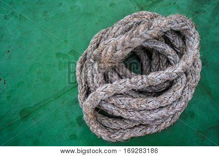 Closeup photo of rope on green boat's deck