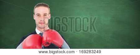 Businessman with boxing gloves against green chalkboard