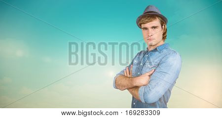 Serious hipster crossing his arms against blue green background