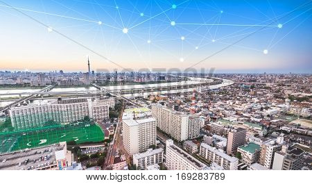 Business concept for information communication connection technology - panoramic modern city skyline bird eye aerial view under dramatic glow and beautiful dark blue sky
