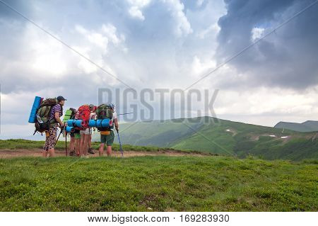 Group of tourists hikers with backpacks standing in mountains considering their destination. Team work consept.