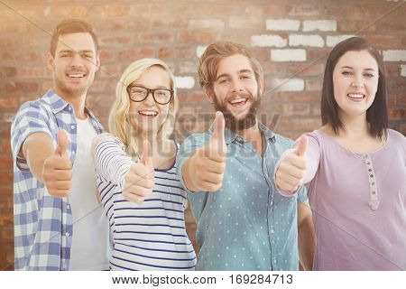 Portrait of cheerful business people with thumbs up against brick wall