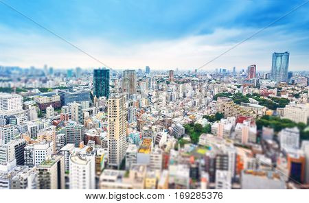 Business and culture concept - panoramic modern city skyline bird eye aerial view from tokyo tower under dramatic grey cloudy sky in Tokyo Japan. Miniature Tilt-shift effect