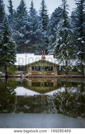 quaint cozy cabin beside a pond in the cold of a snowy morning vertical