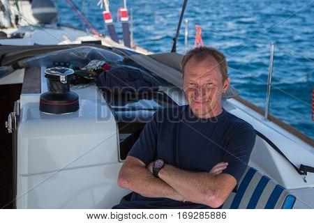 Man skipper sits on his sail yacht. Vacation, sailing, travel.