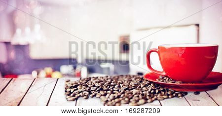 Wooden table against coffee beans and cup