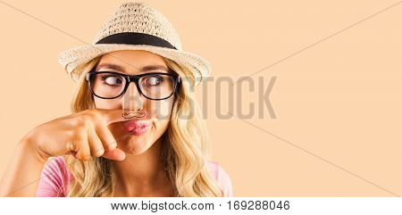 A beautiful hipster having a fake mustache against orange background