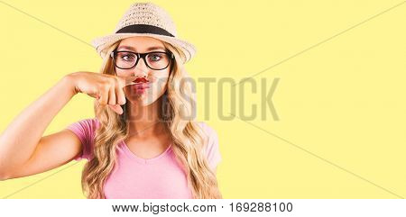 A beautiful hipster having a fake distinguished mustache against yellow background