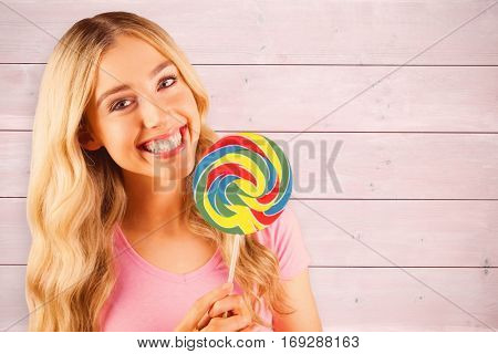 A beautiful woman holding a giant lollipop against bleached wooden planks background