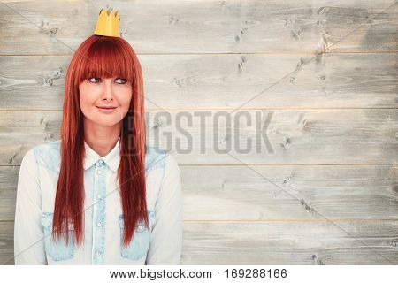Happy hipster woman with a crowned against bleached wooden planks background