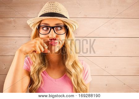 A beautiful hipster having a fake mustache against overhead of wooden planks