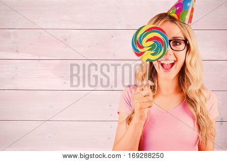 Portrait of a hipster hiding herself behind a lollipop against bleached wooden planks background