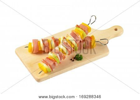 Two raw pork and vegetable skewers