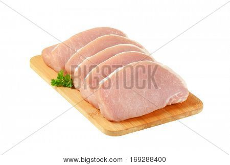 raw boneless pork loin chops on cutting board