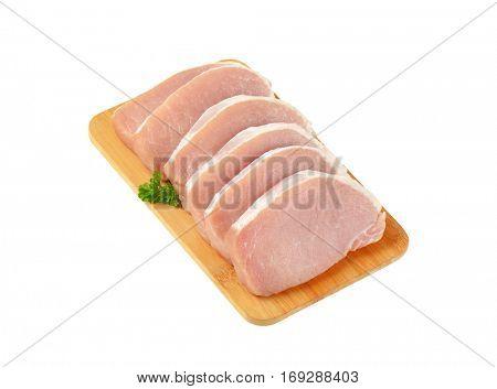 raw boneless pork loin chops on cutting board