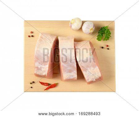 Slices of fresh boneless pork loin on cutting board