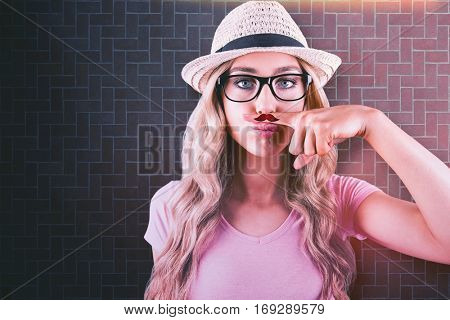 A beautiful hipster having a fake distinguished mustache against textured background