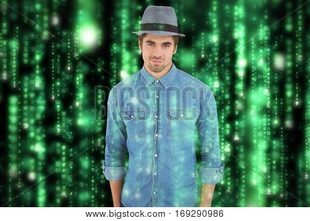 Portrait of confident hipster wearing hat against lines of green blurred letters falling