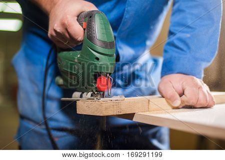 a carpenter worknig with jig saw and wood