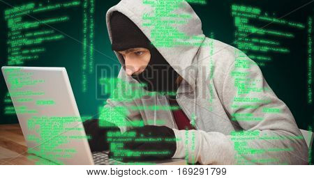 Hacker using laptop against green background with vignette