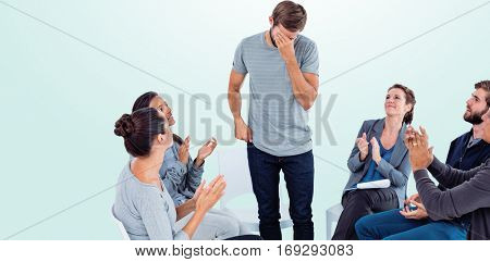 Rehab group applauding delighted man standing up against blue background