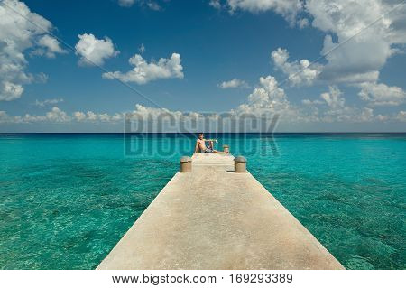 Young man sit on pier in caribbean blue water background. Pier in tropical. Man on vacation