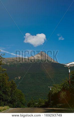 Heart shape cloud under mountain landscape. Road with cloud heart blue sky