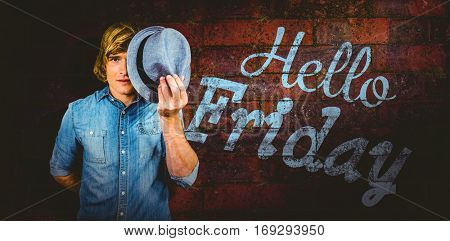 Focused hipster man hiding his face against texture of bricks wall