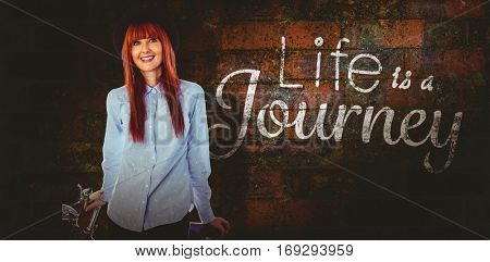 Smiling hipster woman leaning on a bike against texture of bricks wall