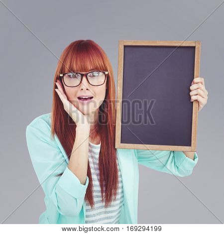 Smiling hipster woman holding blackboard against grey