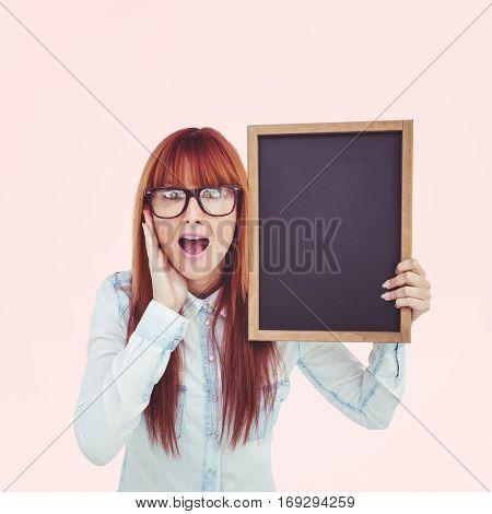 Smiling hipster woman holding blackboard against beige