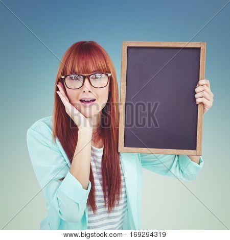 Smiling hipster woman holding blackboard against dark blue green background