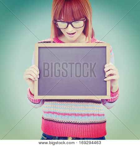 Smiling hipster woman holding blackboard against blue sky