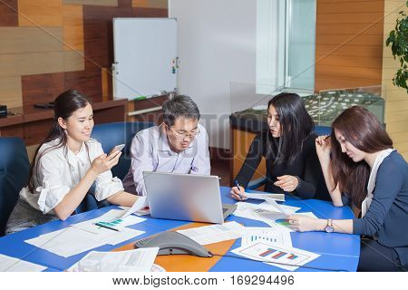 Business meeting Asian people sitting for table with business plan on high floor in the office. business people negotiate