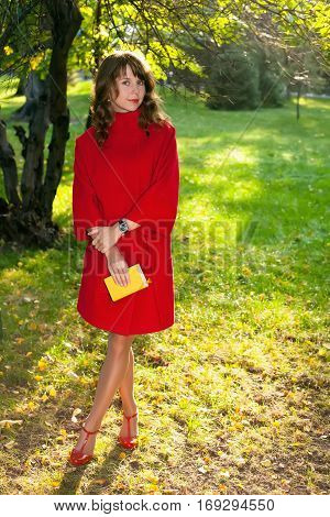 Beautiful woman in red coat posing in autumn Park keeping in hand little yellow book