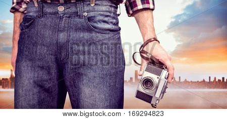 Hipster man holding digital camera against cityscape on the horizon