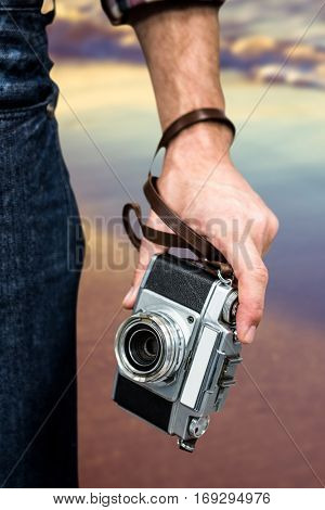 Hipster man holding digital camera against sunset of a beautiful day
