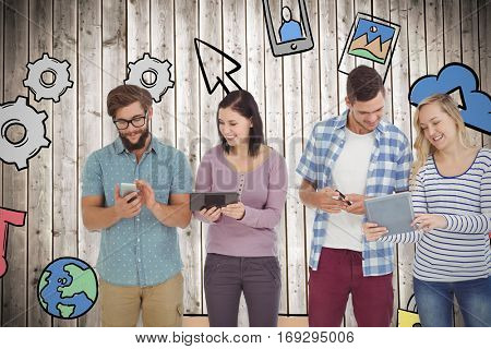 Smiling business people using electronic gadgets against wooden planks background