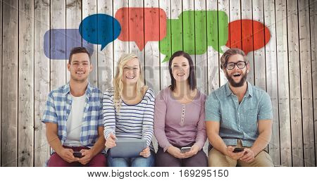 Portrait of smiling business people holding electronic gadgets against wooden planks background