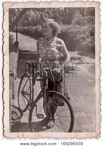 Vintage photo of young woman with a bike (Poland, 1950's)