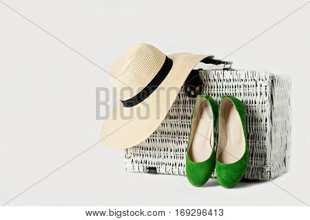 White wicker suitcase a woman's hat and green shoes. Selective focus.
