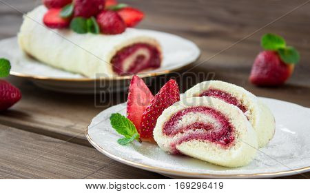 slice of Homemade Sweet roll with Strawberry jam and berries on wooden background