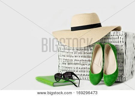 White wicker suitcase womens hat sunglasses green shoes and notepad. Selective focus.