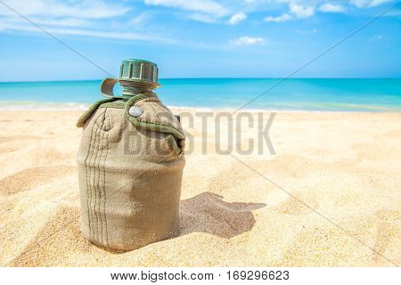 Army water or Military canteen on the sand beach with blue sky