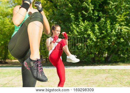 Two fitness girls doing front kicks taebo training