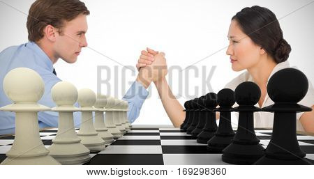 Business couple arm wrestling at desk against white and pawns facing off on board