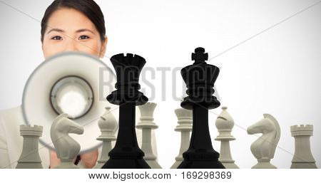 Young businesswoman shouting through a megaphone against black king and queen standing in front of white pieces