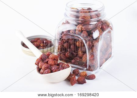 Dried rosehip berries in glass jar on a white background