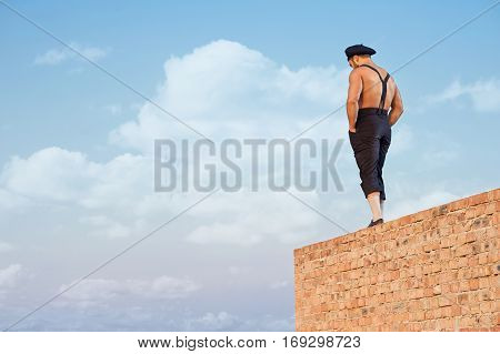 Back view of muscular builder in work wear standing on brick wall on high. Man holding hands in pockets and looking down. Extreme building in hot summer day. Blue sky on background.